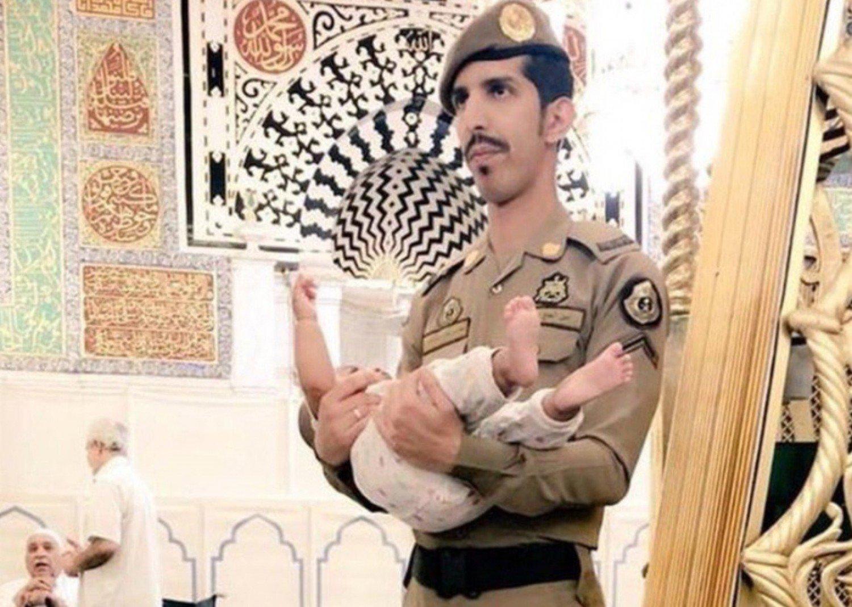 حَمَل الطفل ليُصلي والده.. رجل أمن يثير الإعجاب بالمسجد النبوي